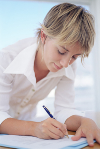 Woman filling in a form --- Image by © Royalty-Free/Corbis